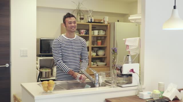 husband to talk with his wife while the housework - 皿洗い点の映像素材/bロール