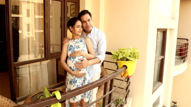 ms husband touching belly and pointing out a view to his pregnant wife while standing in balcony / india - architectural feature stock videos & royalty-free footage