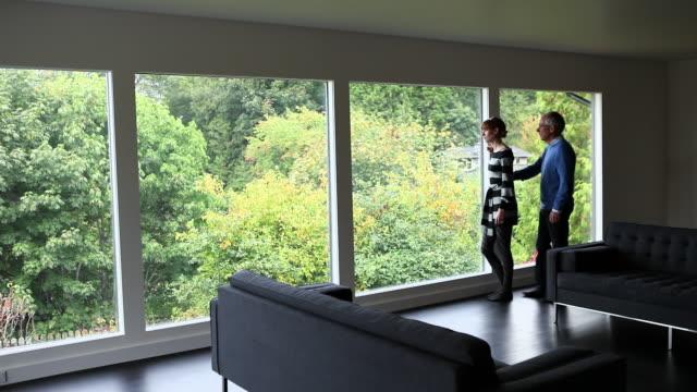 ws husband walking into living room standing with wife near window of home smiling and laughing/seattle, washington, usa - アメリカ太平洋岸北西部点の映像素材/bロール