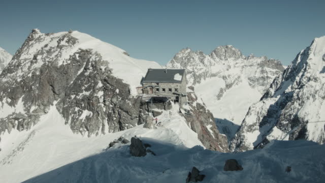 Hut between snow capped peaks in Swiss Alps