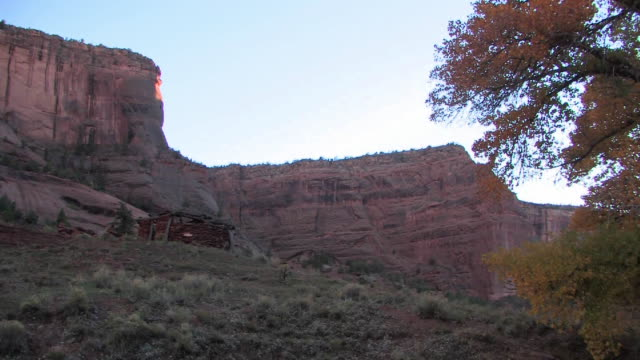 ws hut in shade near canyon walls/ canyon de chelly national monument, arizona - canyon de chelly stock videos & royalty-free footage