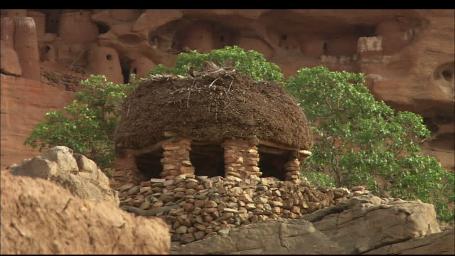 a hut made of rock and mud stands on the edge of a desert ledge in the republic of mali. available in hd. - hut stock videos & royalty-free footage