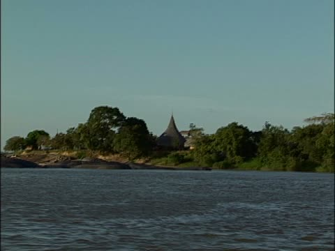 hut on the riverbank - tetto di paglia video stock e b–roll
