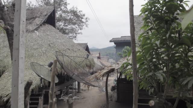 ws pan huts and village / xam neua, laos - tetto di paglia video stock e b–roll