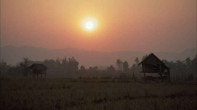 WS Huts in village at sunset, Thailand