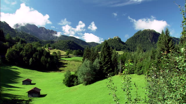 ws zi huts on alpine meadow and ehrenberg castle ruins on top of mountain, tyrol, austria - 山小屋点の映像素材/bロール