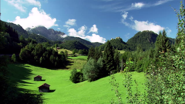 ws huts on alpine meadow with ehrenberg castle ruins in distance, tyrol, austria - 小屋点の映像素材/bロール