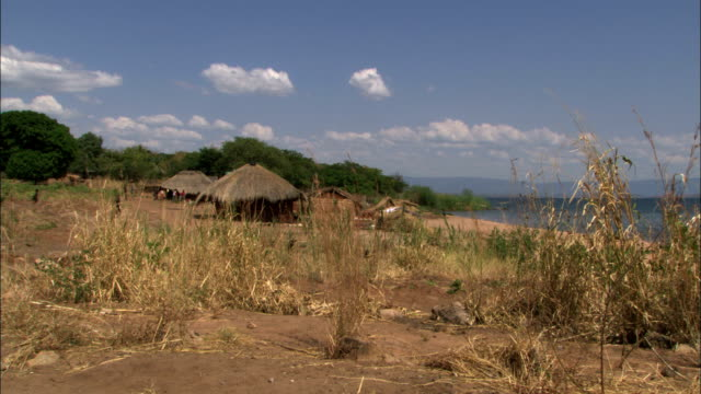 huts sit near the shoreline of mishembe bay. - hut stock videos & royalty-free footage