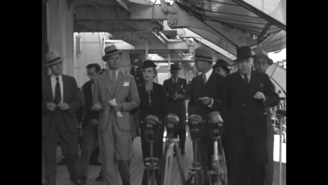 Hutton and Reventlow accompanied by reporters and group of men walking together on deck of ship towards microphones / CU Reventlow and Hutton talking...