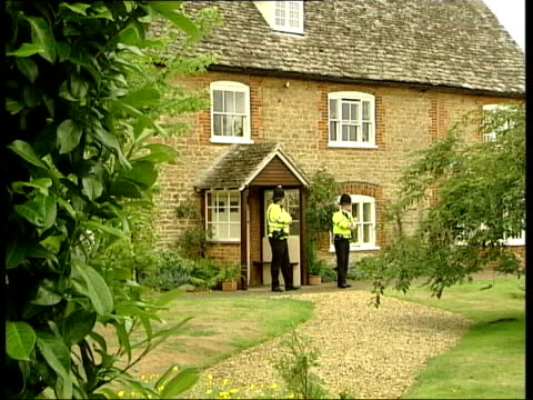 hutton inquiry into kelly's death widow's evidence lib police officers standing guard outside house cms window - widow stock videos and b-roll footage