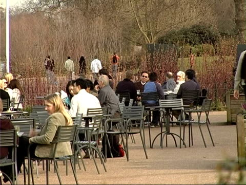 stockvideo's en b-roll-footage met hyde park general views people seated in groups at tables in cafe area talking and young people waiting at pedalo hire area beyond / old woman in... - waterfiets