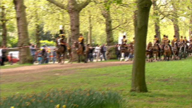 vídeos de stock, filmes e b-roll de london green park ext military band marching sot / ceremonially dressed king's troop royal horse artillery soldiers on horseback pulling cannon... - parque green