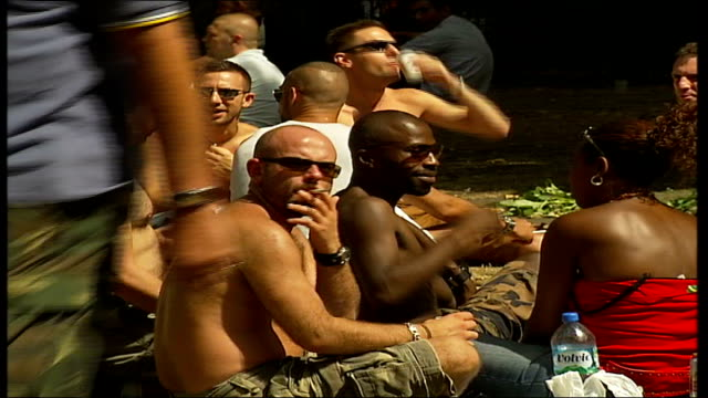 vídeos de stock e filmes b-roll de hyde park sponsored walk for people living with hiv and aids; hyde park: group of men seated on the ground chatting and smoking two men chatting back... - retrovírus