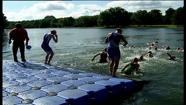 london hyde park ext triathlon competitors wade into the serpentine and begin swimming triathletes cylicng through park triathletes off bikes and... - the serpentine london stock videos & royalty-free footage