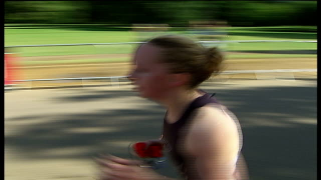 hyde park triathlon; helen tucker interview sot triathletes running triathletes at changeover station after bike race section of race tim don... - triatleta video stock e b–roll