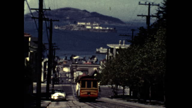 hyde street cable car heads up hill towards camera san francisco bay alcatraz and angel island in background - san francisco bay stock videos & royalty-free footage