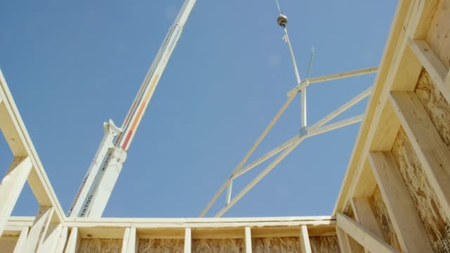 vídeos de stock e filmes b-roll de a hydraulic crane lowers a framed wooden roof truss into place on a framed house at a construction site on a clear, sunny day - baixar
