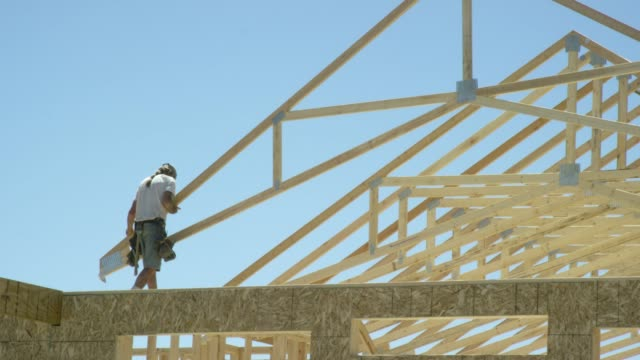 a hydraulic crane lowers a framed wooden roof truss to a caucasian male construction worker in his forties who guides it into place while framing a house on a clear, sunny day - construction frame stock videos & royalty-free footage