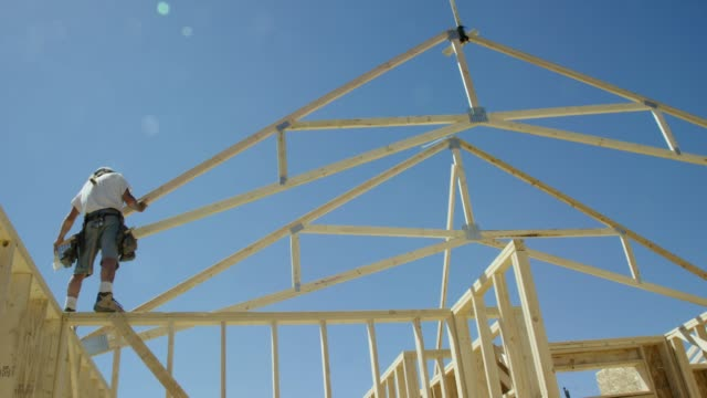 a hydraulic crane lowers a framed wooden roof truss to a caucasian male construction worker in his forties who guides it into place while framing a house on a clear, sunny day - home ownership stock videos & royalty-free footage