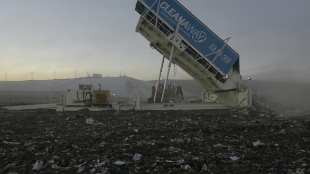 stockvideo's en b-roll-footage met a hydraulic tipping platform empties garbage from a truck trailer into a landfill cell at the melbourne regional landfill site operated by at... - afvalverwerking