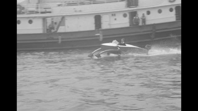 Hydrofin boat invented by Christopher Hook turns tight circles in New York Harbor power boats tied along pier / hydrofoil skis protrude in front of...
