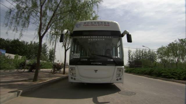 WS REAR POV Hydrogen fuel cell bus driving down street, Beijing, Beijing, China