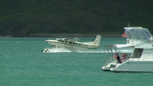 MS Hydroplane moving past anchored boat in bay, Whitsunday Islands, Queensland, Australia