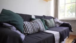 Hygge or Lagom concept - a cozy sofa with a lot of pillows and blankets with bedspreads