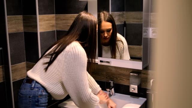 vídeos de stock e filmes b-roll de hygiene and skincare. woman in bathroom washing hands standing - mulher bonita
