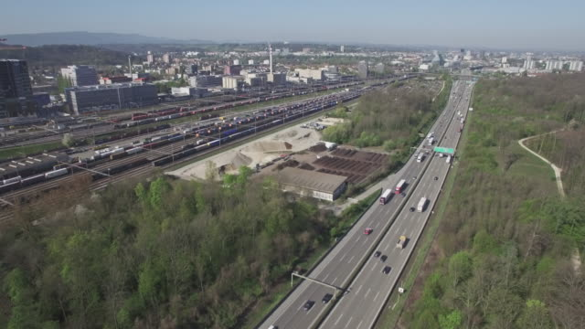 hyper lapse aerial shot highway, city, train station and industry - zeitraffer stock videos & royalty-free footage