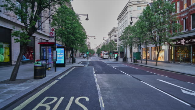 a hyper lapse along oxford street, central london uk,  devoid of people and traffic at dusk - high street stock videos & royalty-free footage