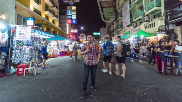 4K Hyper lapse of Attractive young Asian tourist man traveling at Khaosan Road walking street among people in Bangkok, Thailand., Travel and Outdoor market concept