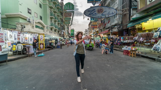 4K Hyper lapse of Attractive young Asian tourist woman traveling at Khaosan Road walking street among people in Bangkok, Thailand., Travel and Outdoor market concept