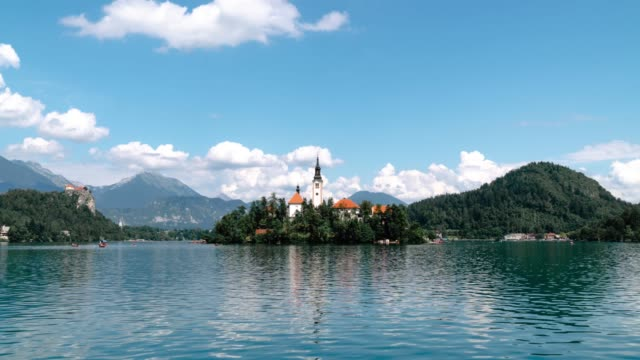 vídeos de stock e filmes b-roll de hyper lapse of bled island with church of the assumption of mary and bled castle on lake bled at clear summer day. travel and adventure concept. mountains background. beautiful place of slovenia - lago bled