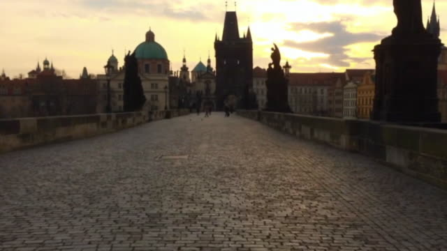 Hyper lapse of people walking over the Charles Bridge in Prague, crossing the Moldava river on early morning during sunrise in a new day in the city.