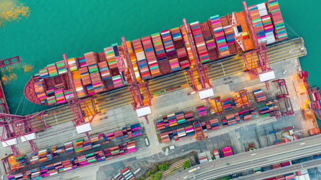hyper lapse or dronelapse of international port with crane loading containers in import export business logistics in hong kong - docks stock videos & royalty-free footage