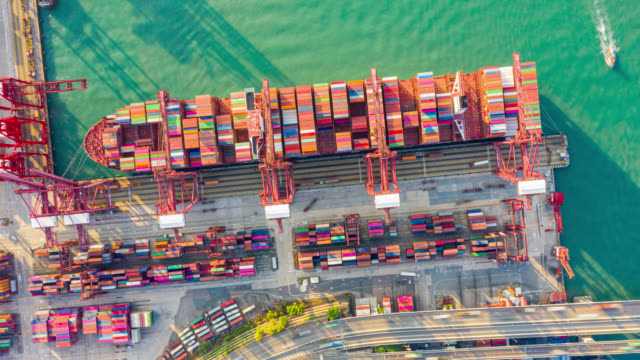 hyper lapse or dronelapse of international port with crane loading containers in import export business logistics in hong kong - harbour stock videos & royalty-free footage