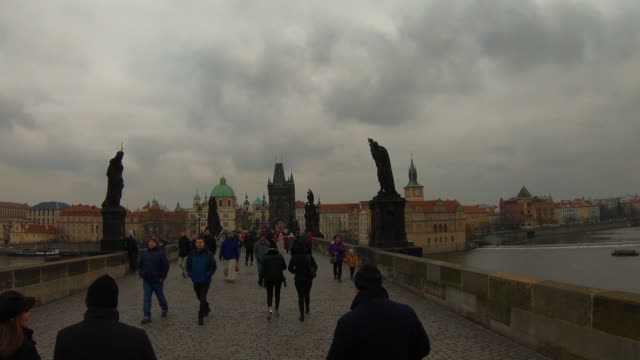 hyper lapse recorded walking in the charles bridge of prague with cityscape and crowd of tourist people walking visiting the city in winter with cloudy day. - charles bridge stock videos and b-roll footage
