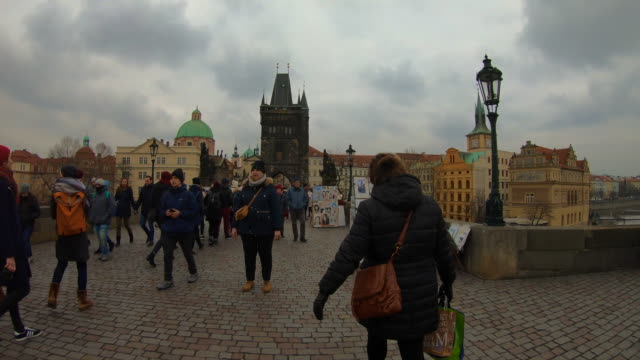 Hyper lapse recorded walking in the Charles Bridge of Prague with cityscape and crowd of tourist people walking visiting the city in winter with cloudy day.