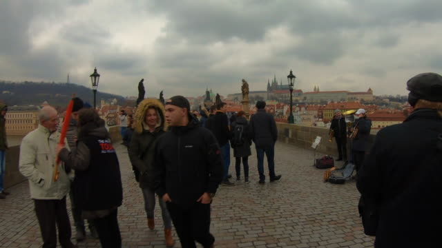hyper lapse recorded walking in the charles bridge of prague with cityscape and crowd of tourist people walking visiting the city in winter with cloudy day. - cobblestone stock videos and b-roll footage