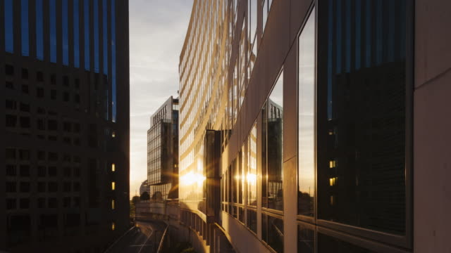 hyper lapse / time lapse at sunrise along corporate buildings in financial / business district la défense in paris - edificio adibito a uffici video stock e b–roll