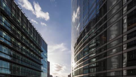 vídeos y material grabado en eventos de stock de hyper lapse / time lapse at sunrise along corporate buildings in financial / business district - reunión de negocios