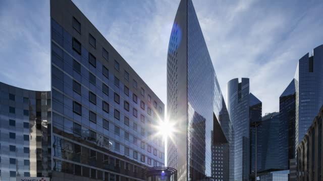 vidéos et rushes de hyper lapse / time lapse at sunset through corporate buildings in financial / business district - façade