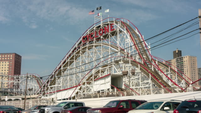 hyper lapse, time lapse footage at coney island brooklyn, ny. featuring the famous cyclone rollercoaster, wonder wheel, and thunderbolt. - coney island stock-videos und b-roll-filmmaterial