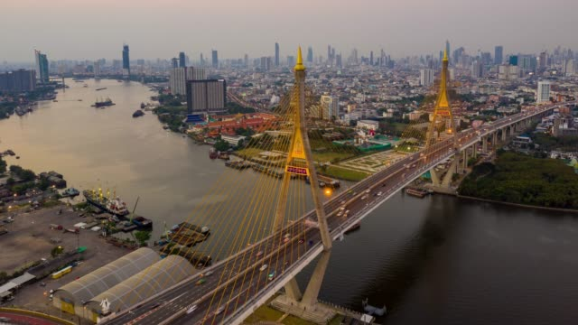 hyperlapse aerial view of bhumibol suspension bridge cross over chao phraya river in bangkok city with car on the bridge at sunset sky and clouds in bangkok thailand. - bangkok stock videos & royalty-free footage
