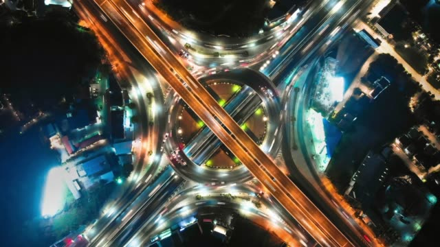 hyperlapse : aerial view of expressway road intersection at night - construction site stock videos & royalty-free footage