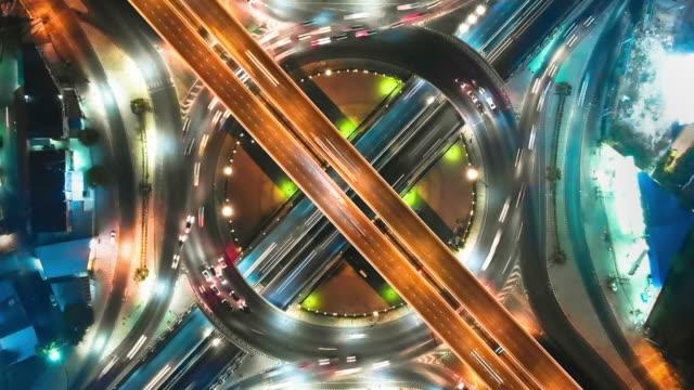 vídeos de stock, filmes e b-roll de hyperlapse: vista aérea da interseção da estrada de expressway na noite - hyper lapse