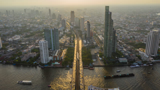 Hyperlapse aerial view of the Bangkok landmark financial business district with skyscraper over Chao Phraya River at Bangkok Thailand in sunset