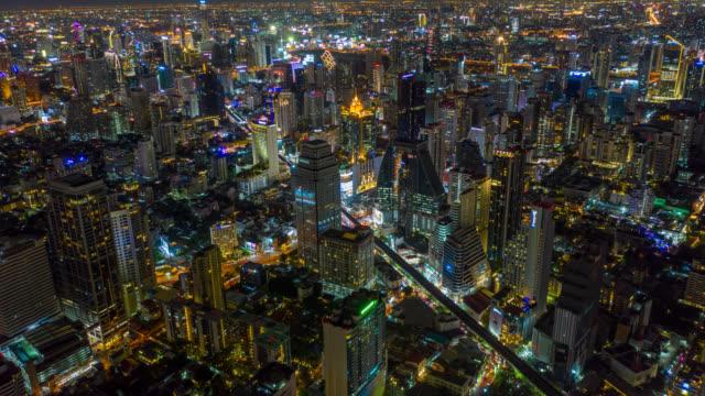 vidéos et rushes de vue aérienne d'hyperlapse du quartier financier d'affaires de point de repère de bangkok avec le gratte-ciel sur le secteur d'asoke dans la ville de bangkok la nuit - voie urbaine