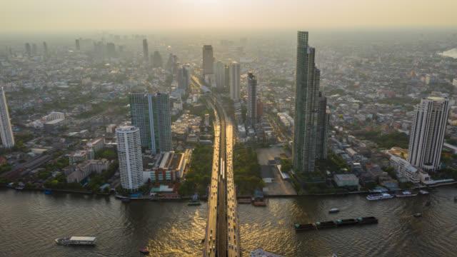 日没時にバンコクタイのチャオプラヤ川の上に超高層ビルを持つバンコクのランドマーク金融ビジネス地区のハイパーラプス空中写真 - bangkok点の映像素材/bロール